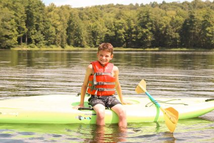 A boy in a green kayak on the lake