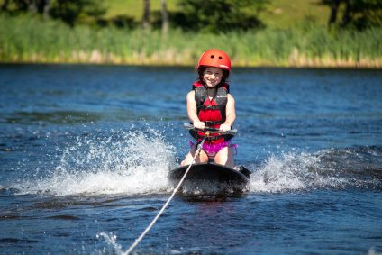 A camper on a waterski in the lake